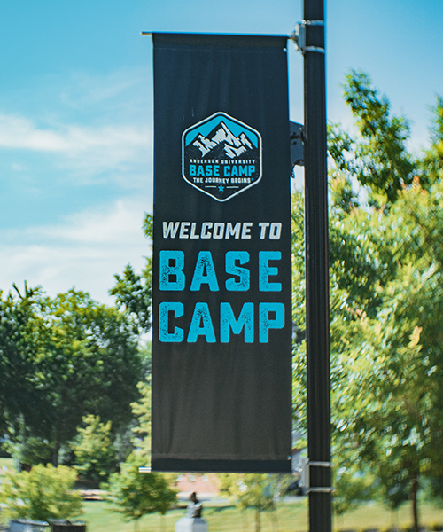 A photo of a Base Camp banner attached to a lamp post on campus