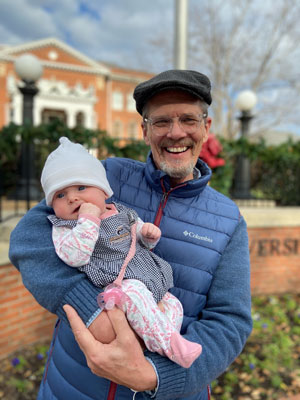 Dr. Larson holding Cora Joy on Campus