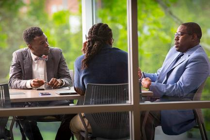 Professor meeting with three students in conference room