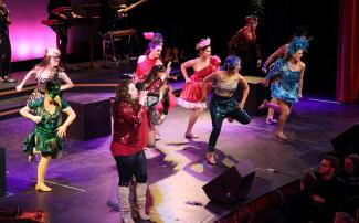 Multiple students in costume dancing on stage